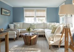 Muted cornflower blue, beadboard walls give this living room a cozy, nautical look. Neutral furniture and decor look crisp and chic against colorful walls.