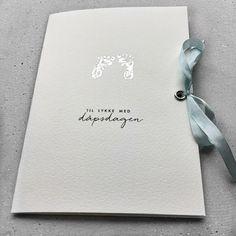 Dåpskort til gutt. Kortet er håndtrykket med et babyfotavtrykk i sølv og pyntet med en nydelig lys blå sløyfe i ekte matt silke.