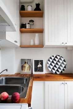 I like the contrast of the wood shelves (and how they pick up on the butcher block counters) and the white cabinets.