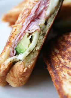 Grilled sandwich with ham, mozzarella, avocado and pesto.
