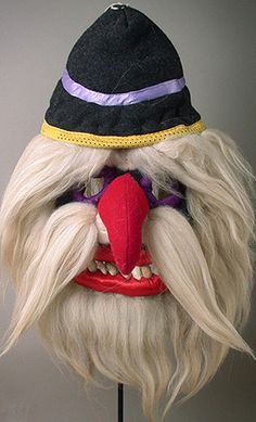 This Romanian Folk Mask is made of cloth, human hair and beans. These masks were used historically for initiation purposes and fertility rituals. In the modern age they are used for large holiday celebrations to represent characters from folk mythology. They are worn solely by men and to speak the name of the mask bearer while in costume is forbidden. This particular mask was made by Albu Ion of the Bucovina region.