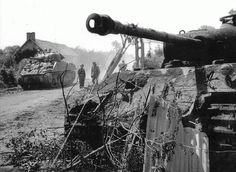 A Sherman Tank passes by the knock out Panzer Tank somewhere in Italy