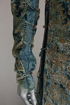 A fine and rare Mariano Fortuny stencilled velvet gown, early 20th century, `labelled Mariano Fortuny, Venise', the soft blue velvet ground stencilled in gold with Medieval style patterns, the sides inset with pleated silk and laced with silk cords and fastened with Murano glass beads. Detail