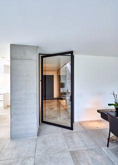 Moderne glazen pivotdeur zonder vloerveer of inbouwelementen in de vloer.