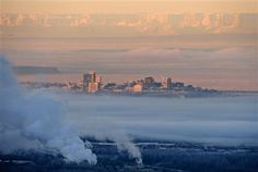 Low clouds blanket Anchorage, Alaska, east of downtown on Friday morning, Dec. 7, 2012. An optical illusion known as Fata Morgana distorts the view of the mountains west of Cook Inlet. Alternating warm and cold layers of air bend light to create the effect. (AP Photo/The Anchorage Daily News, Marc Lester)