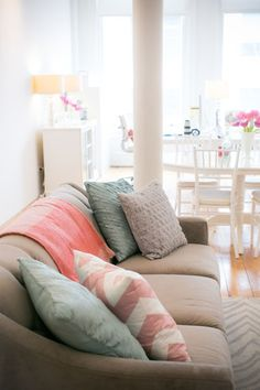 This is almost exactly what I envision!  Beige couch with coral, teal, and gray accents, white furniture!