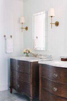 Bathroom. Bathroom with tiled mirrors flanked by Thomas O'Brien Bryant Sconces in Hand Rubbed Antique Brass situated above his and her vanities accented with brass faucets topped with white marble and paired with tiled mirrors. Natalie Clayman Interior Design.