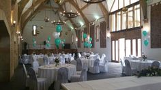 Silver sashes on white chair cover with balloons at Haselbury Mill