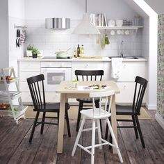 A small white kitchen with a small dining table in white stained solid birch, black chairs and a white junior chair.