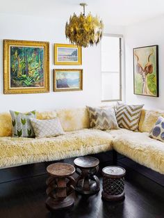 A bright living room with a corner bench, vintage art work, and a vintage chandelier | NyDomaine