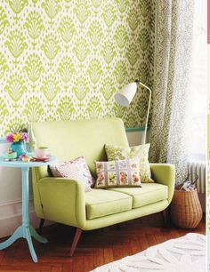 green patterned wallpaper and mid century modern furniture.