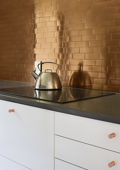 In the kitchen, copper-colored stainless steel tiles from TileBar create a glowing backsplash. The cabinetry is by IKEA, the countertop is Caesarstone, and the induction cooktop is by Bosch. #smallspace #catskills