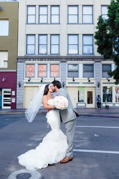 The groom gracefully kissed the bride on the street. #WeddingCouple #WeddingPhotography Photography: Full Spectrum Photography. Read More: http://www.insideweddings.com/weddings/a-modern-san-diego-hotel-wedding-with-purple-sparkling-details/672/