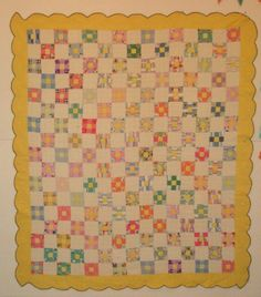Vintage nine patch quilt with scallop border.  Each nine patch center is same yellow as border, and four print squares, and four solid squares that coordinate with print.