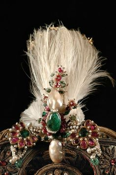 State Cap, India, 19th century. Gold wire embroidery, feathers, rubies, pearls and emeralds. This state cap is reputed...