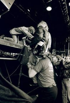 Kurt Cobain getting some help up on stage by security guard and Thurston Moore of Sonic Youth.  :)