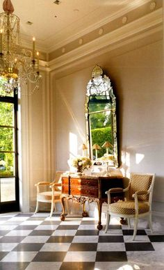 Black and white tiles, chandelier and large mirror, that is quite an entrance hall.