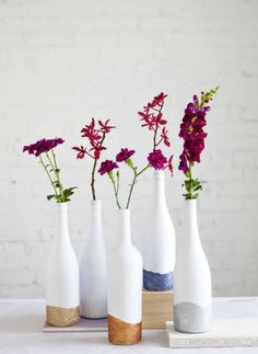 Give empty wine bottles new life by dipping them in glitter + using them as vases.