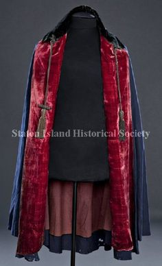 1840s Man's cape made of navy blue wool with black and red velvet trim, red velvet facing and brown wool lining. The cape has a round neckline with a black velvet collar, a long braid attached at the back of the collar with a tassel at each end, and hook and eye front closure.