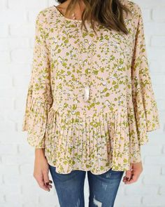 This blouse is adorable and incredibly feminine in this blush hue. Our Ivy Hill Crisscross Blouse has taupe and cream florals throughout with an adorable pleate