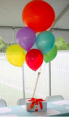 Great centerpiece for kid parties - wrap a box with pretty paper and tie balloons on top. via Pizzazerie {Up inspired party}