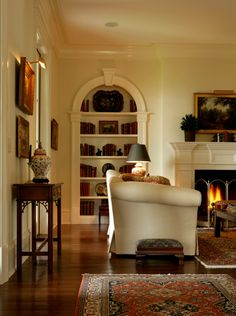 gorgeous traditional space with fireplace, built-in arched bookshelves, vintage rugs, overstuffed sofa