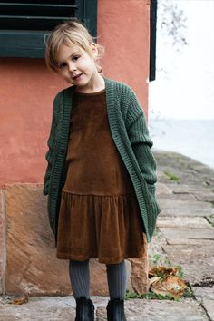 Soft dark mélange caramel coloured velour dress in organic cotton with large flair in the skirt and slim sleeve. Opens in the back with one push button. Combined with a soft and warm Llama Patent Cardigan