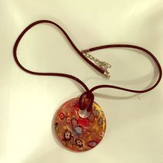 """Colorful glass pendant necklace. A lovely gold-on-red glass pendant, with multi-colored flowers, on a suede necklace. 18"""" on shortest fastening, the pendant sits about 2"""" below the collarbone. Never worn, in excellent condition. Back of the pendant is red, showing the base glass. Jewelry Necklaces"""