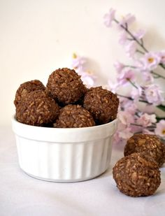 Rice krispies peanut butter balls in a bowl, with two balls next to it and some flowers in the background