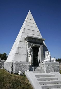 The Egyptian Revival tomb of Lucien Brunswig stands out because of its pyramidal shape and sphinx sculpture. Architectural details such as a flared surround for the entry gates and a cavetto, or concave cornice, over the doorway also speak to the Egyptian Revival style.