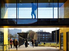 pupils exit burntwood school as one pupil walks along a glass-sided walkway above