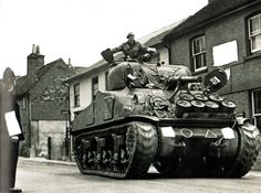 A British Army Sherman Tank rumbles down a street on it's way to a south coast portprior to the Normandy landings of June 1944 (D-Day). The wartime Censor has obliterated a sign in the background as well as the tank's unit markings - UK - 1 June 1944