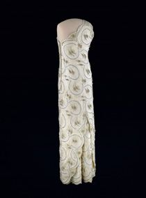 """Nancy Reagan wore this white beaded one-shouldered sheath gown of lace over silk satin to the 1981 inaugural balls. It was designed by James Galanos, who also designed the one-shouldered white gown Mrs. Reagan wore to her husband's first gubernatorial inaugural ball. In interviews, Galanos said that he wanted to make Mrs. Reagan look glamorous, """"... elegant and in keeping with the new formality."""""""