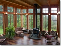 -Rainy Hill House -Warm colors due to stained wood -Sconces b/t windows Custom Home Designs by Ross Chapin Architects