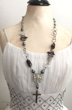 This vintage assemblage necklace is a chunky, statement design featuring a vintage repurposed Art Deco rhinestone accent with bright, clear rhinestones. To this rhinestone accent Ive attached a vintage Italy religious cross accent with silver finish. The necklace sections feature chunky amethyst nuggets, rock crystal nuggets, gray and purple pearls, a vintage filigree heart link, vintage rhinestone accent and various chain sections. The closure is a hand forged hook and eye design made of…