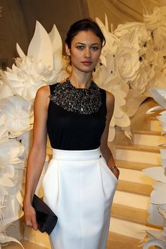 Olga Kurylenko at Chanel. White skirt, black top and that's what I'd call a statement necklace! Lol