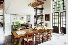 A 17th-century portrait overlooks the kitchen table, which is surrounded with antique French chairs | archdigest.com