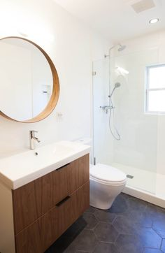A California Spanish Revival home gets a fresh new bathroom space, with gray hex tile, white subway tile, and walnut vanity, with custom drawer fronts from Semihandmade. Interior Designer: Destination Eichler.