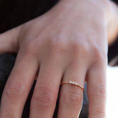 This gorgeous three stones stacking ring is hand-forged in 14k gold will be made with your desired birthstones and material. The delicate ring band measures 1 mm thick, making this ring ideal for stacking. We recommend this ring if you plan on wearing this ring every single day for life (ie. wedding/engagement ring), if you are hard on your jewelry, or if you are a size 8 or above. Please write to the note for seller the stone you want .(You can choose white cz, black cz or any other sto...