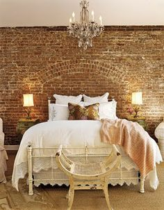 Brick accent wall with chandelier and lace beddings.