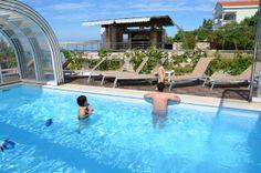 Swimmingpool with retractable cover in front of Barbati apartments house, Novalja, island Pag, croatia