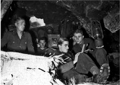 Piper with papers in the foreground, under a kerosene lamp hanging on the ceiling of the cave