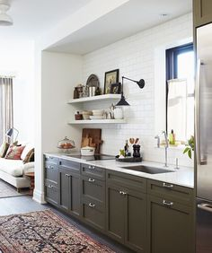 Painted lower cabs, simple stone, subway all the way up, unexpected sconce, warm boho rug.