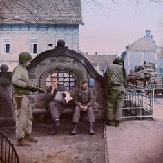Two Americans of the 2nd Armored Division guarding German prisoners near the bridge over the Bega river in the town of Lemgo, North Rhine Westphalia, Germany. 4/5th April 1945. (This could be the 66th...