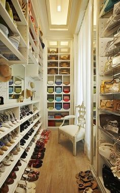 I don't know what I like more about this picture: the fact that it's a massive walk-in closet with a lounge chair or that this person's shoes and shirts are organized by color.