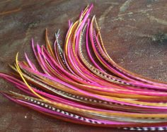 This is a beautiful feather extension with real feathers including magenta grizzly, magenta solid, natural grizzly, cream, and black. There are 6 feathers in this extension that are 9-12 inches long with 3 grizzly feathers. The extension is slightly layered and has a total length of 11-12. These are soft flowing quality feathers and can be treated just like your hair.    6 feathers are bonded at the tip, with a salon glue to create one long extension. If you wish to have your feathers sent…