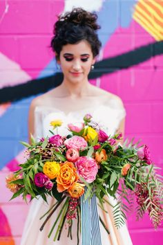 Bright pops of colour in this loose style bouquet with roses and ranunculus.  Yellow, pink, orange by Juli Vaughn Designs.
