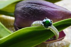 A sparkling .96 carat round tsavorite garnet in a 14K white gold with side diamonds in a bead setting.
