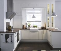 Eclectic kitchen with white shaker cabinets, pendant light, dark floors and counters, stainless appliances... all IKEA