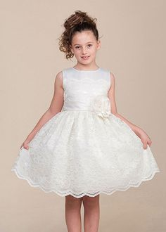 Make her special occasion even grander in this lovely lace dress. Fitted with a satin bodice and lovely lace overlay, this look will prove stunning for any special occasion including Easter, Flower Girl Dresses and Graduations. The skirt is elegant with all over lace and has a girlish charm with underneath netting. Finishing the look on this tea length gown is full lining and an adorable hand rolled flower accenting the waist. Made in USA Item: cy982